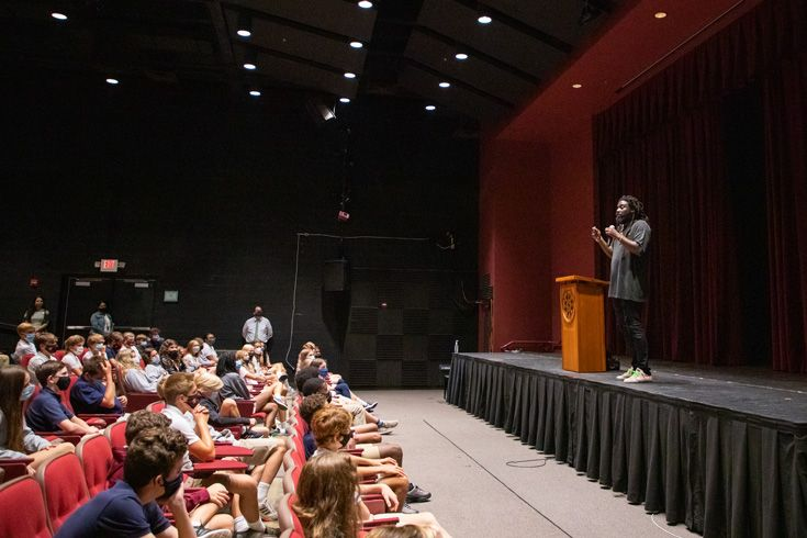 Author Jason Reynolds on stage speaking to Severn School middle schoolers in Price Auditorium.