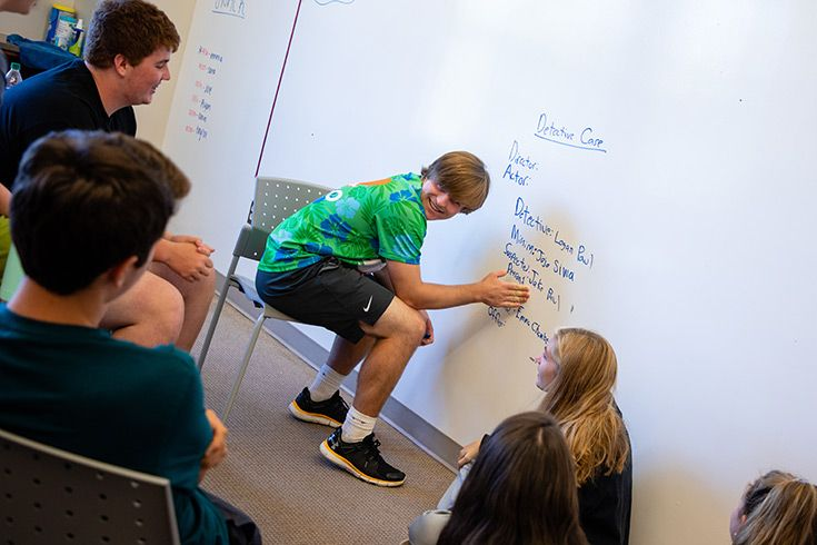 Severn School high school students work in a group and write on a white board.