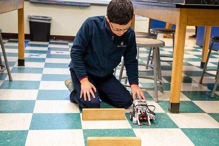 Severn School student showing demonstrating a programmable LEGO Mindstorms robot.