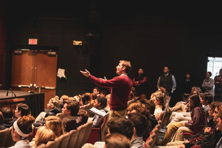 Severn School music director conducting the chorus during a performance.