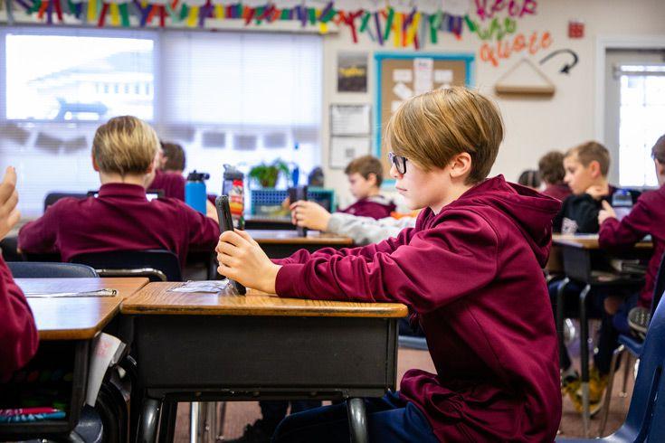 Severn School Lower School student looks at his iPad.