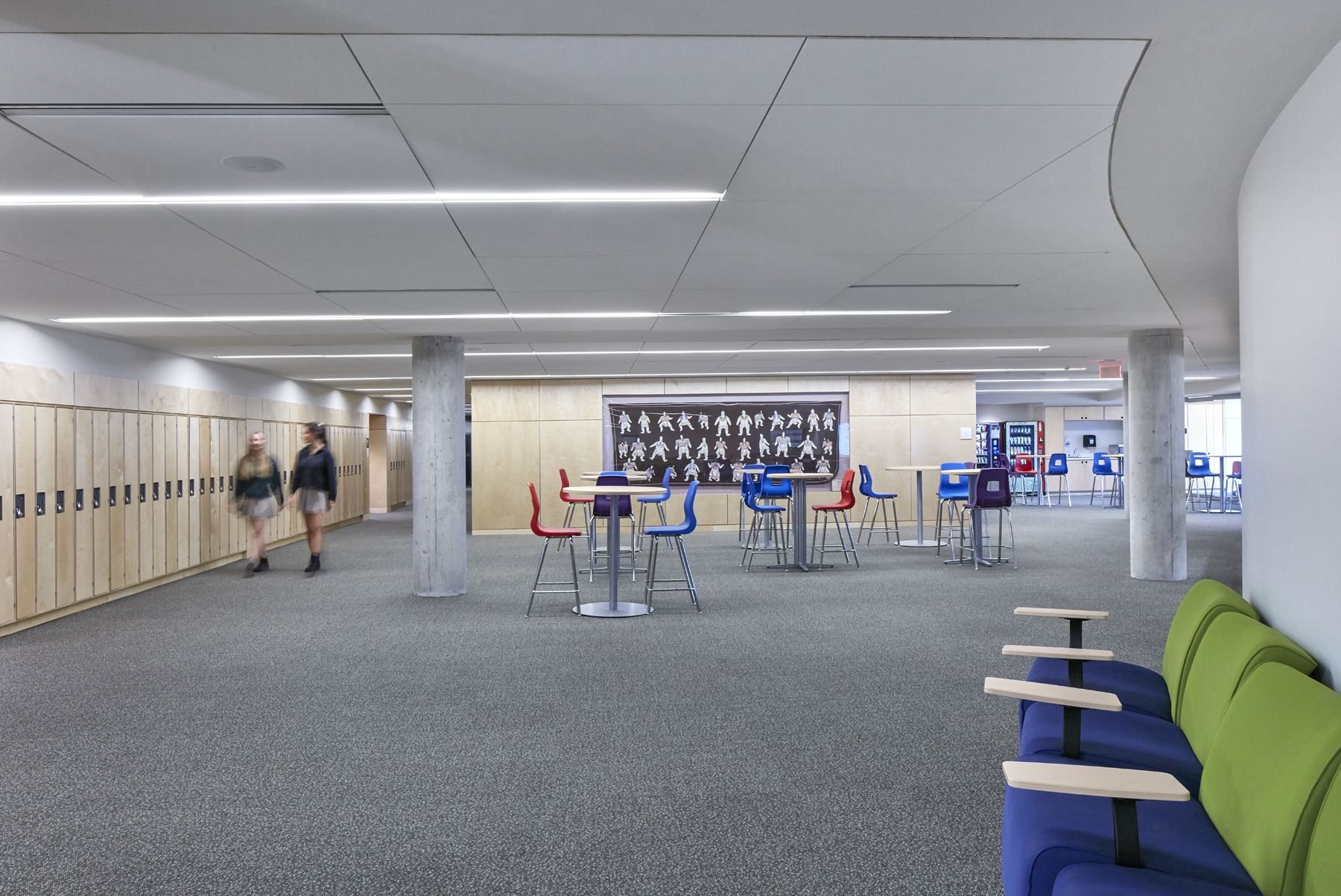 Our second-floor social space provides lots of space for students to gather, including cruiser tables, glass-walled breakout rooms, computer bars and soft seating.