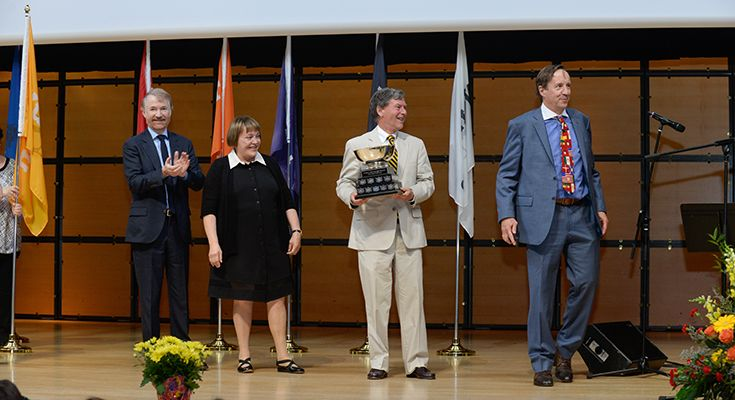 "Greenwood founders Richard Wernham, Julia West and David ""Lub"" Latimer, along with founding principal David Thompson, present the House Cup at the 2017 Celebration Day ceremony."
