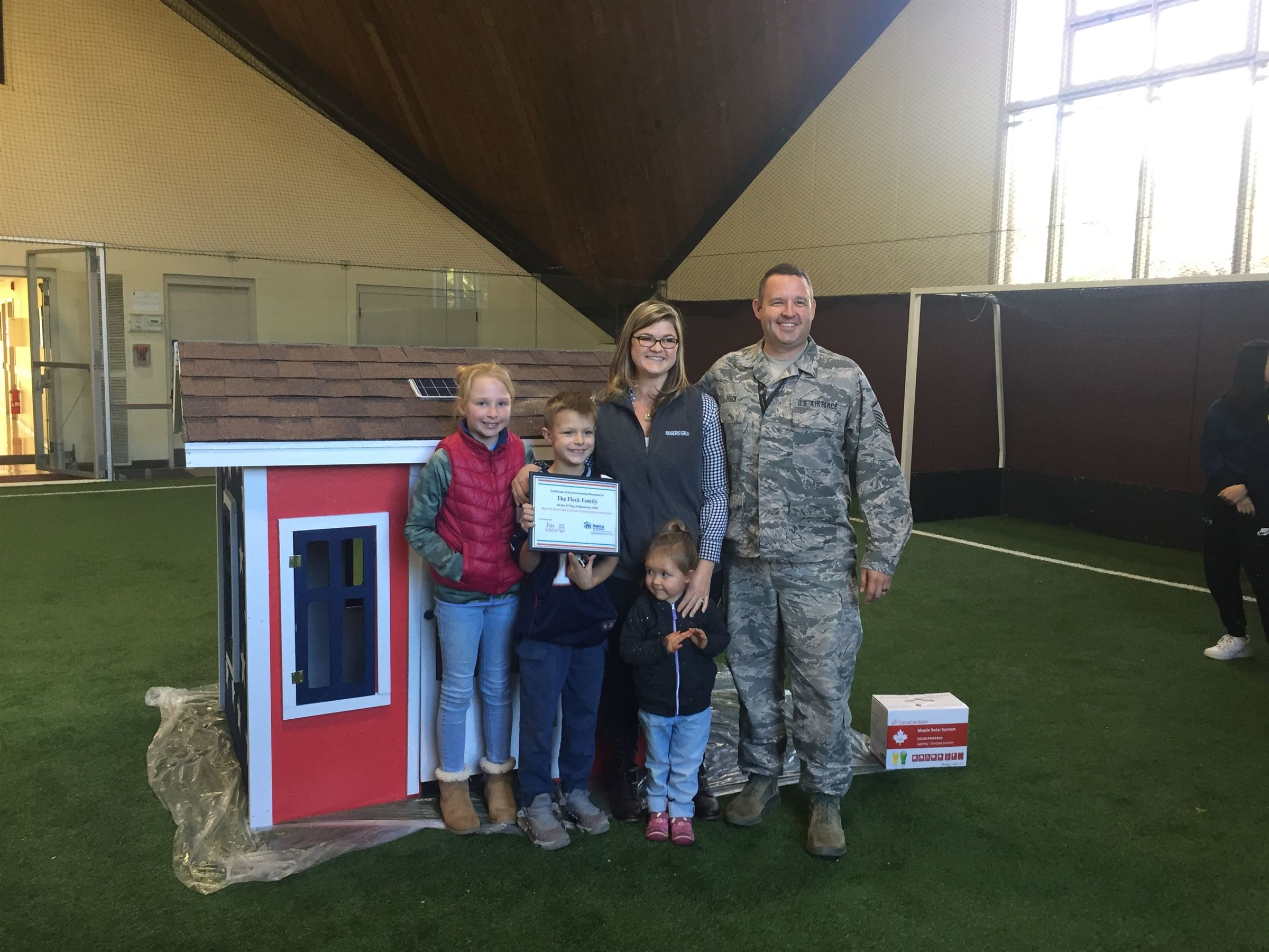 The Fleck Family and the playhouse that Upper School students built for them through Habitat for Humanity's Operation Playhouse.