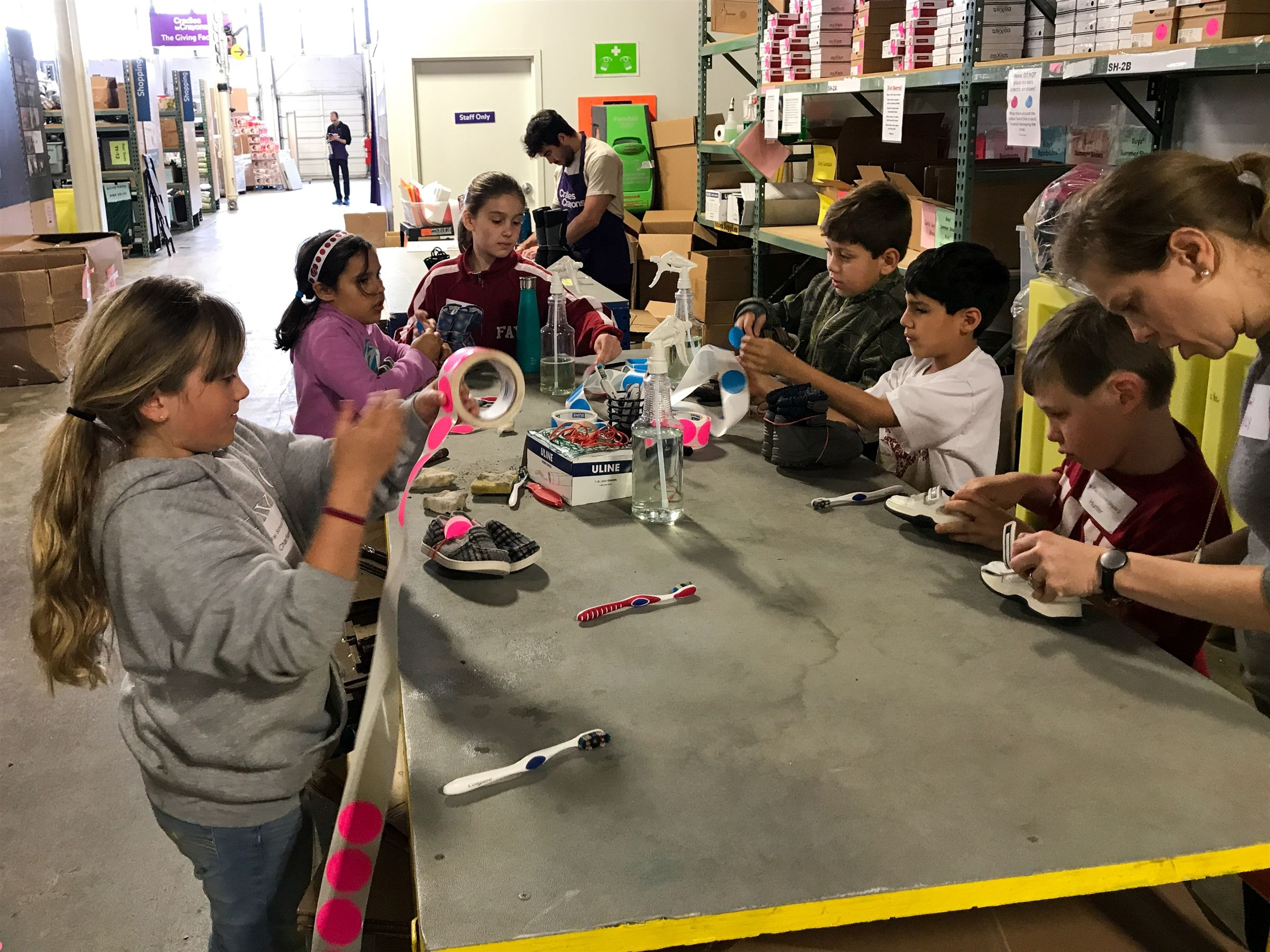 Second grade students sorting clothes and toys at Cradles to Crayons, a local nonprofit that collects and distributes clothing and school supplies to disadvantaged children.