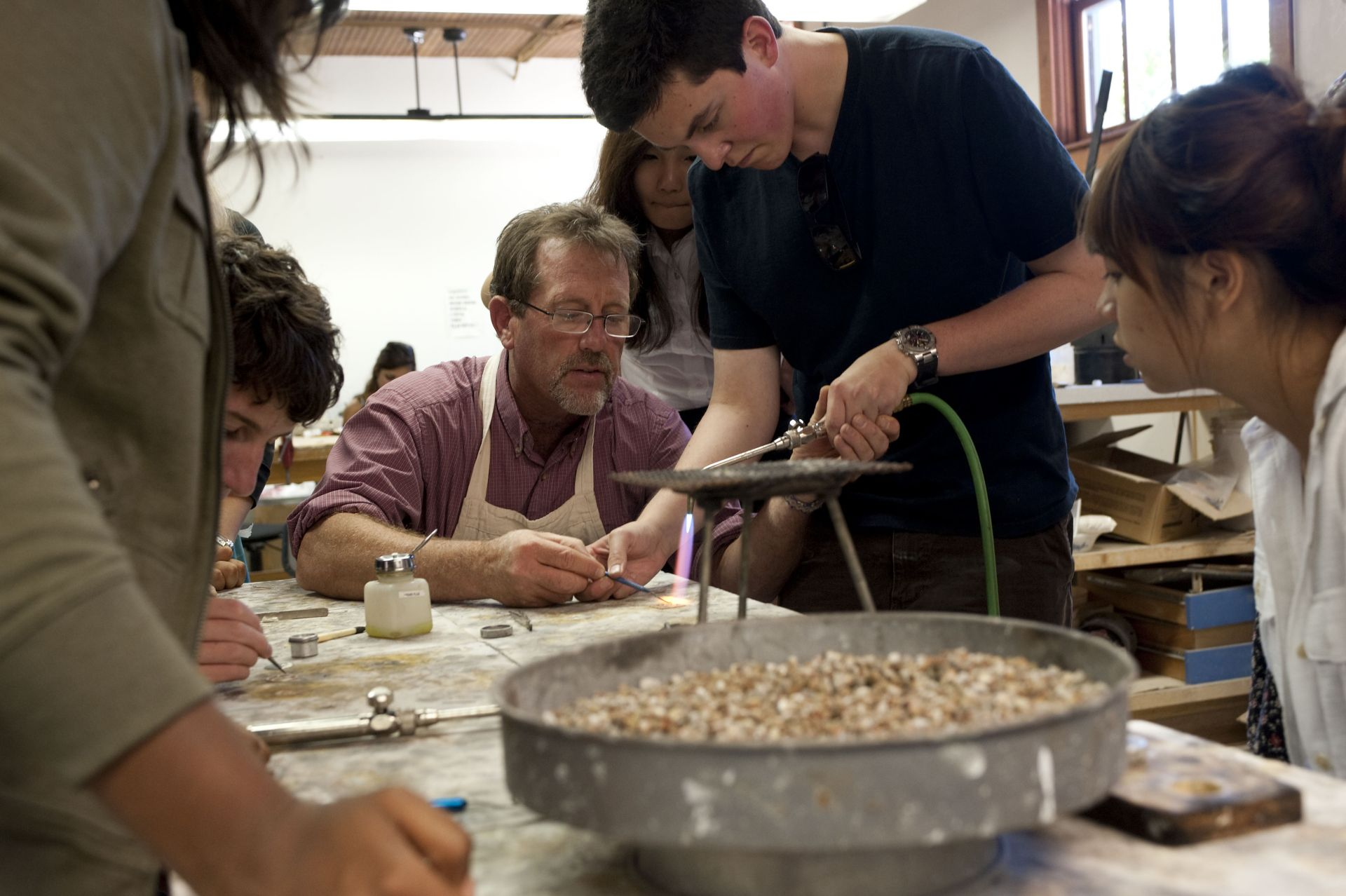 Arts Department Chair Mark Dillon works with students to create beautiful jewelry pieces.