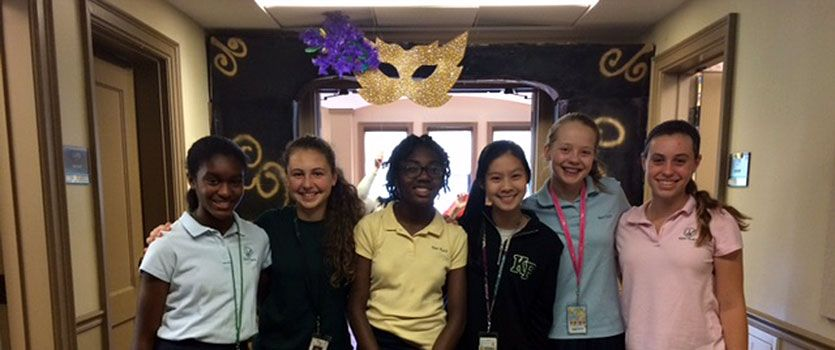 Students in the STEM elective course celebrate their constructed arch for the eighth-grade semi-formal dance.