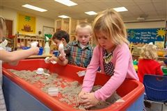 "In one of our lively Preschool classrooms, Junior Pre-Kindergarten students experiment with ""goop"" at the sensory table. Through dynamic, hands-on activities that the children love, we teach the beginnings of literacy, math and science."