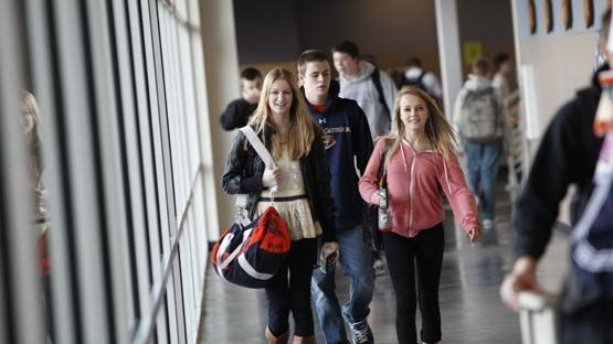 Students transition between classes through corridors flooded with natural light.