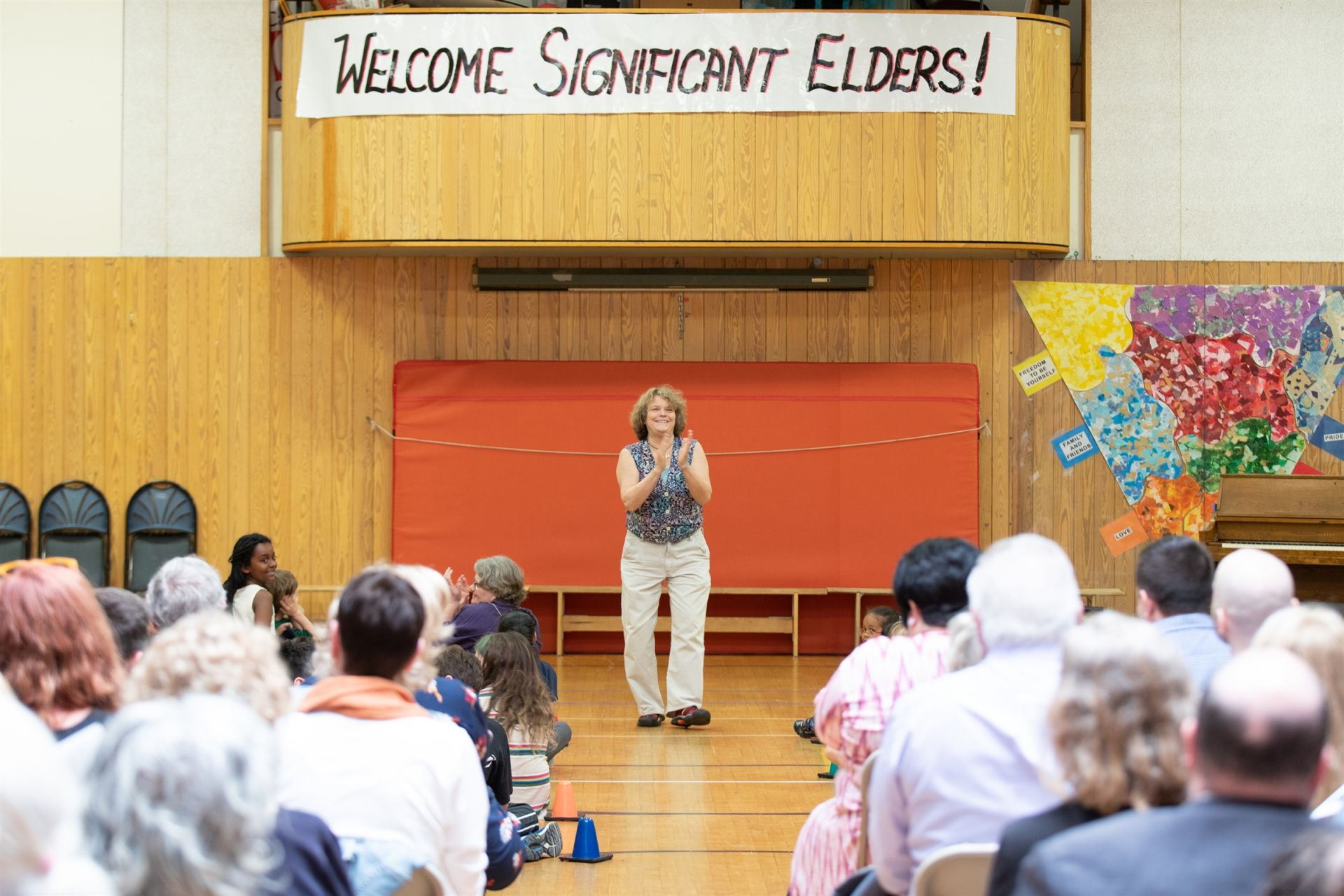 Marytha opens the assembly for Significant Elders Day. A sign in the background says,