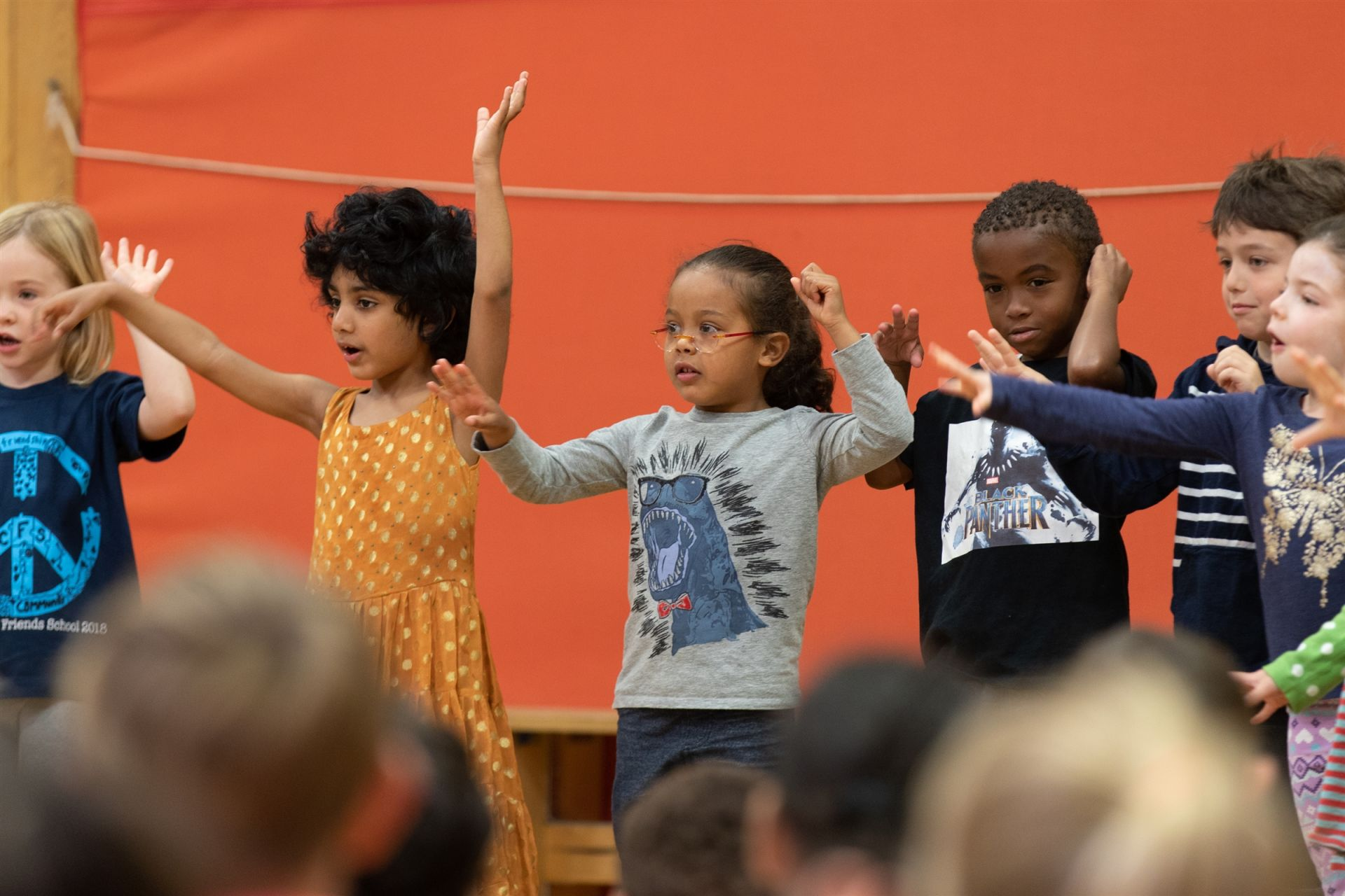 Pre-K and Kindergarten students sing a song with arm motions for the Significant Elders Day assembly.