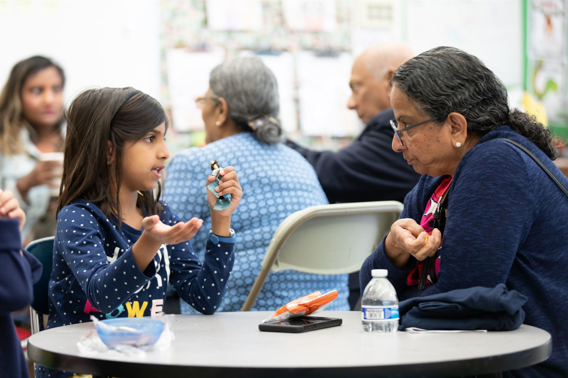 A first-grade student tells a story to her significant elder over a snack.