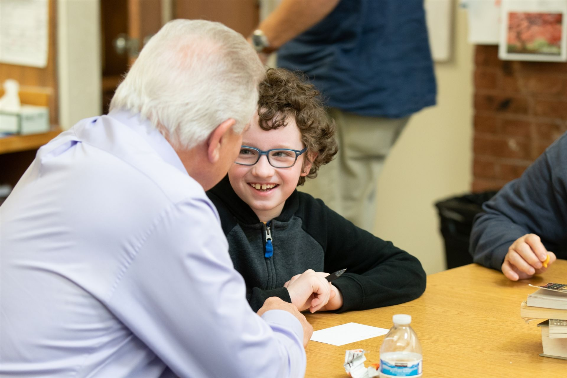 A student with glasses smiles at his significant elder.
