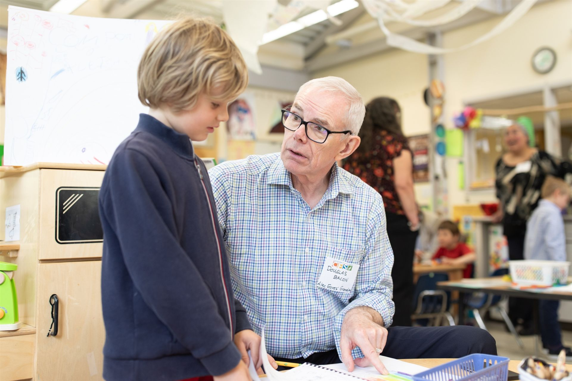A Kindergarten student and his significant elder discuss something written on a page.