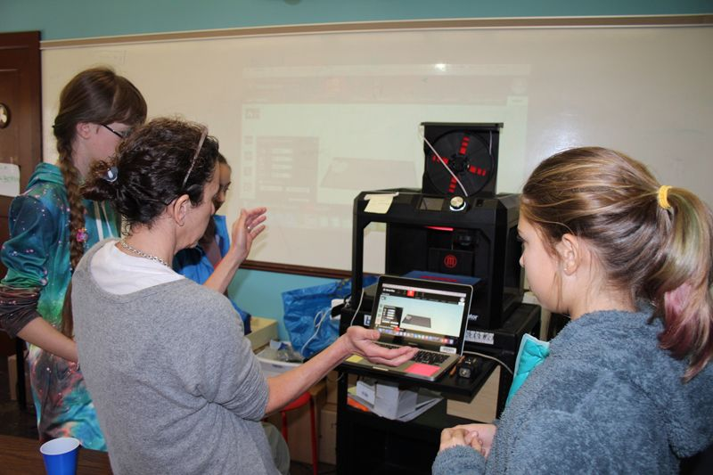 Students learn how to operate a 3-D printer.