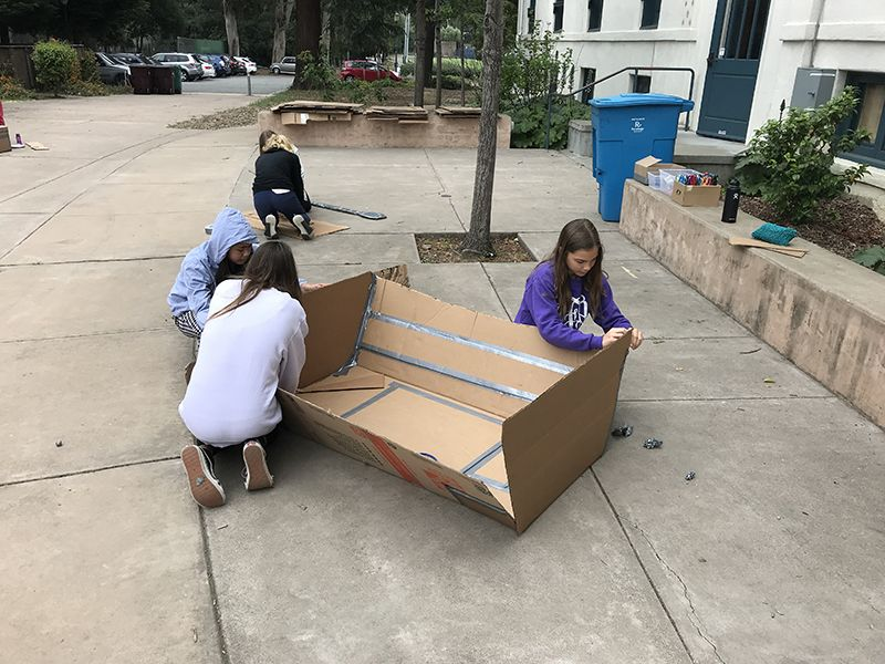 Seventh graders are in the final stages of constructing their cardboard boats for the challenge for an adult to paddle across the length of a pool in their design.