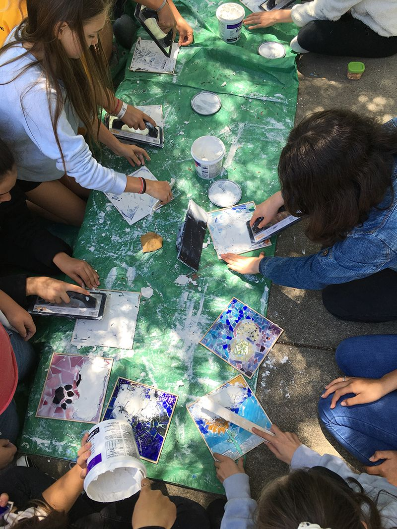 The final touch for their mosaic project is grouting in 6th Grade Art class.