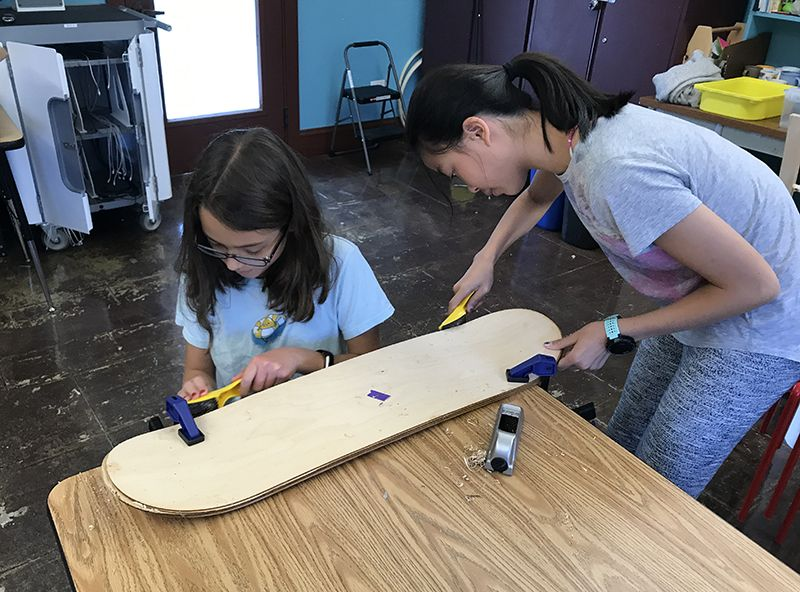 Seventh graders using rasps to finish the edges of the their skateboards in STEAM class.