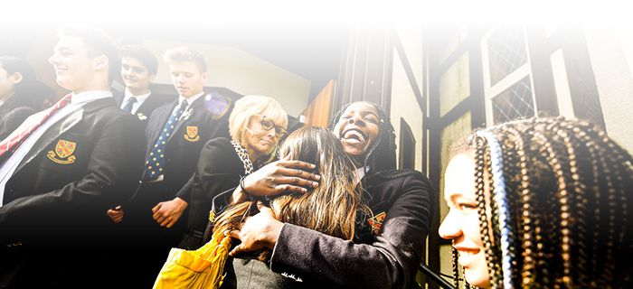 Students embraces in front of chapel