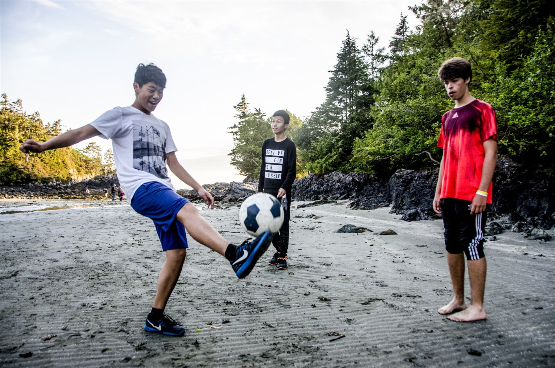 Prep students from Brazil and China play soccer on the beach during a midterm break camping and surfing trip to Tofino.