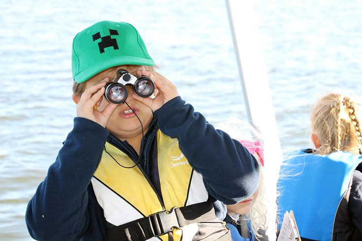 Student on a boat looking through binoculars