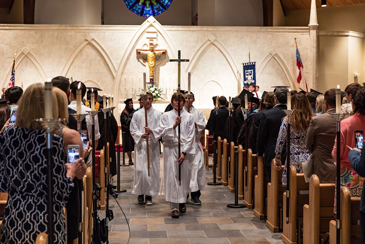 Student servers walking down the aisle with the cross