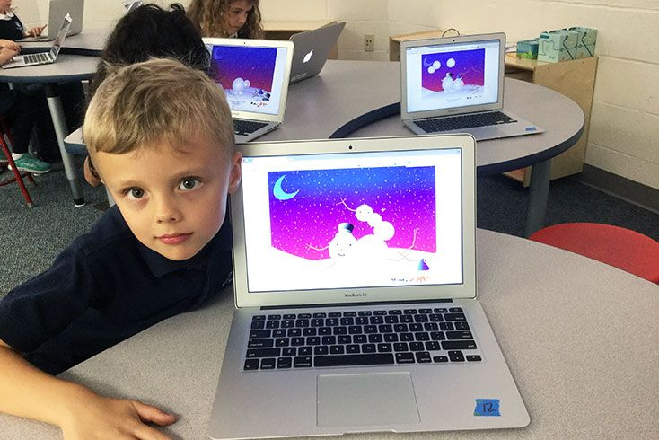 A lower school student with a computer