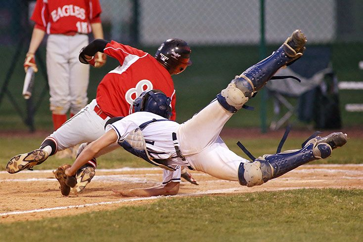 Baseball catcher diving to tag out a runner