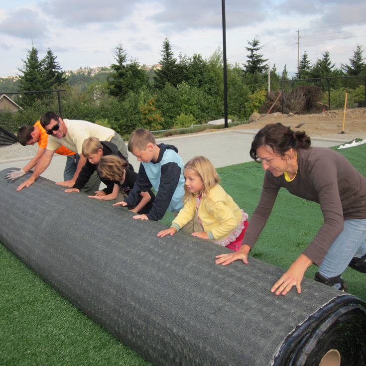 Rolling out the turf field, 2011