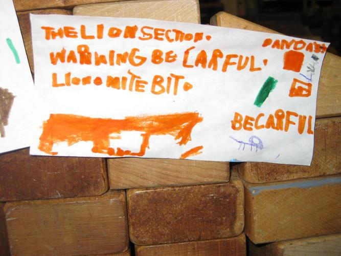 A zoo made in blocks includes warning signs of dangerous animals.