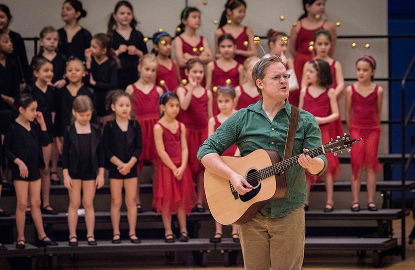 Mr. Hennessee accompanies Grade 2 students at their annual music and dance concert.