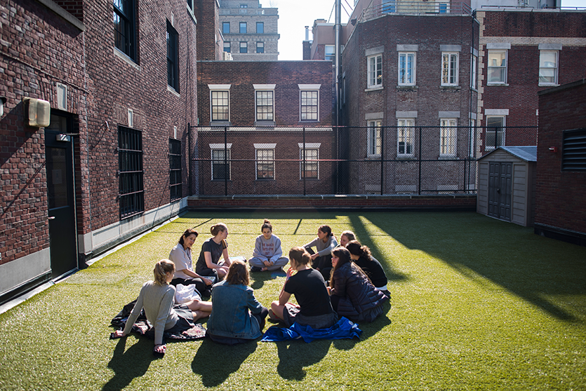 A teacher meets with a group of students in the sun on the 4th Floor Terrace.