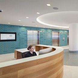 A modern, inviting open-area lobby with touchscreens and adjoined parent lounge
