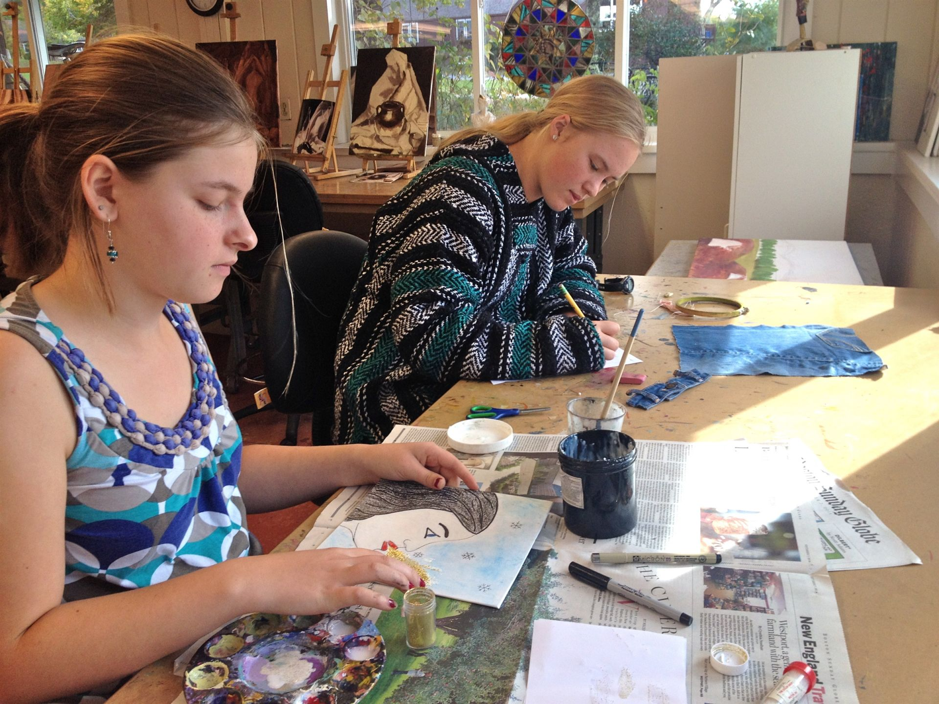 Amelia adding gold glitter and Nicole embroidering on their book covers. Very original!