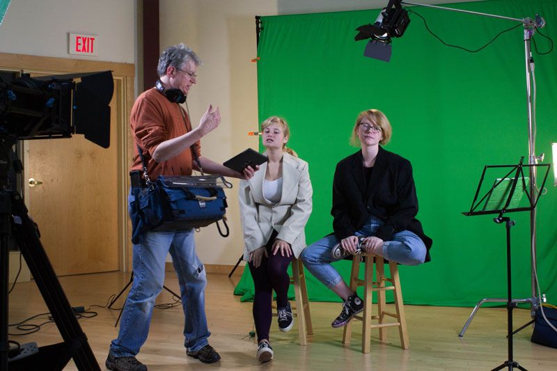 Film Making Teacher Jim McClure going over lines with Elsa Schloemer '17 and Fiona Pelz-Sharpe '17 for their film