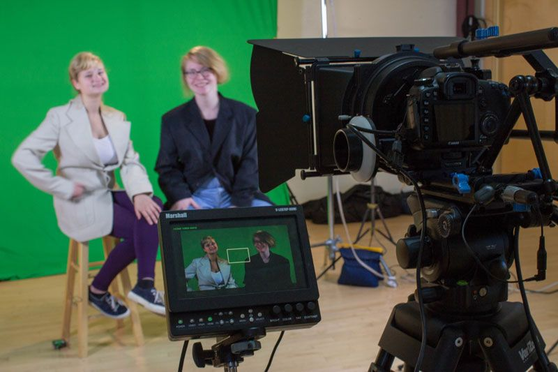 Elsa Schloemer '17 and Fiona Pelz-Sharpe '17 in frame in front of a green screen in between takes for