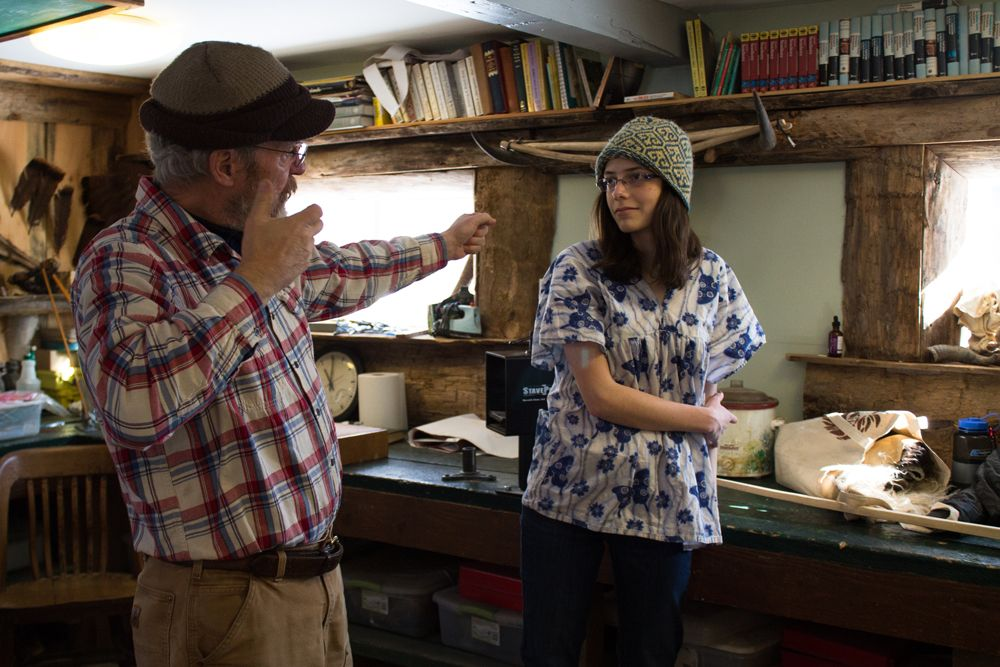 Naturalist teacher Keith Badger indicates how a bow is drawn as he and Audrey Quick '17 discuss the next steps in creating her own English Longbow.