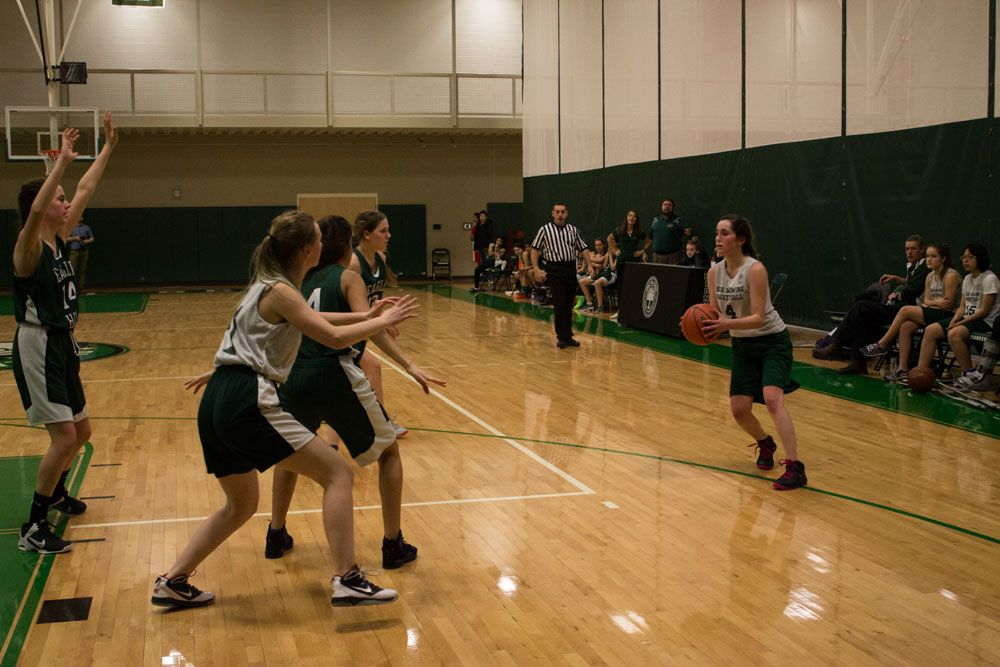 The Girls' Basketball Team plays against Eagle Hill School. Allie Heins '18 looks for someone to pass to.