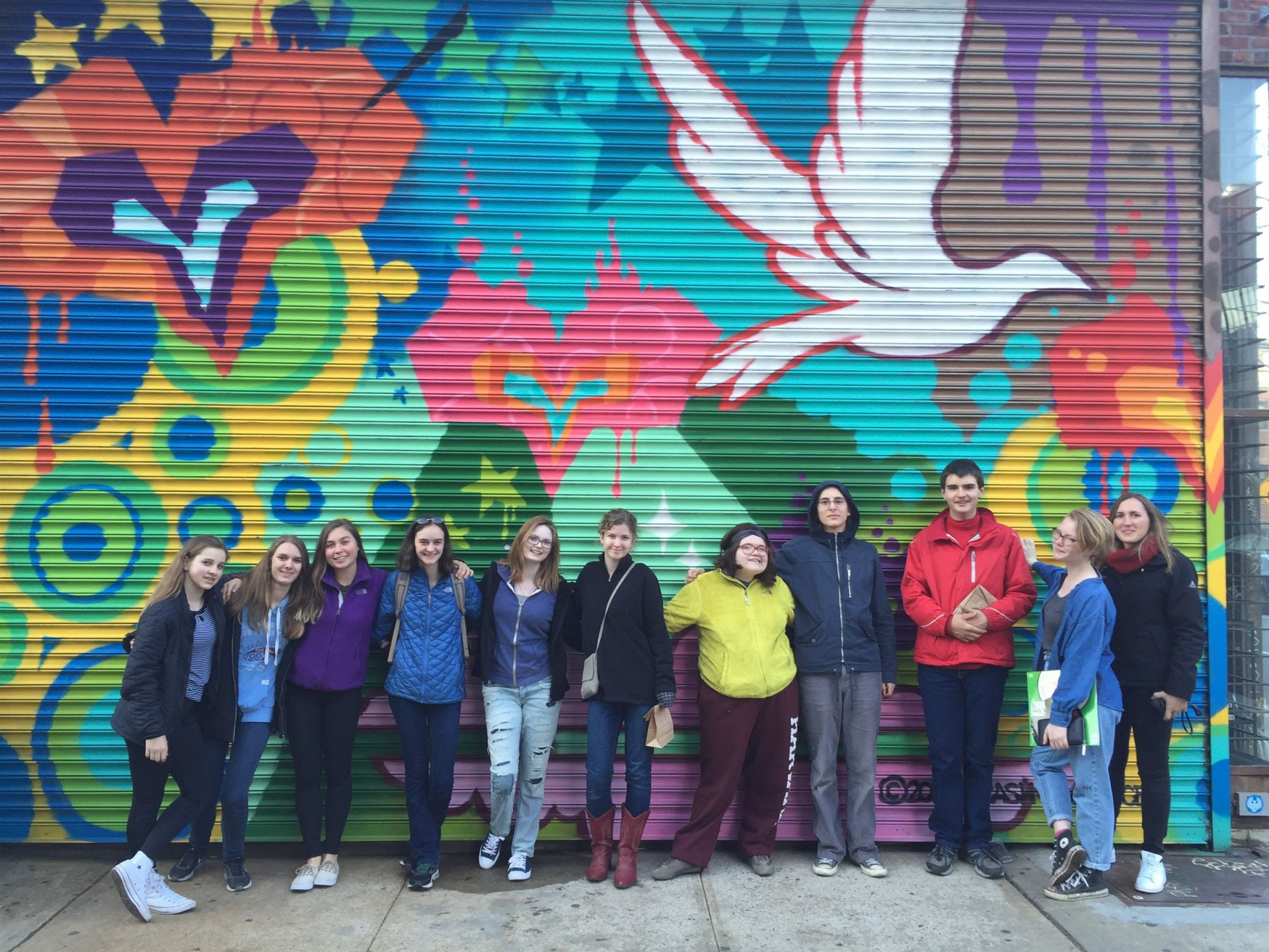 The group stands in front of street art in Brooklyn, New York City, New York.