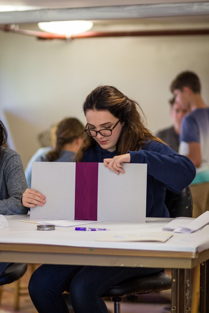 Zoe Rezsutek-Bush '20 puts the finishing touches on her binding. The students will use these journals for the rest of the class and turn in their observations and notes at the end.