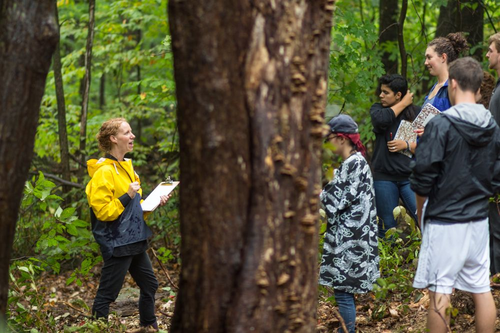 Naturalist teacher Emily Turner addresses the Trimester of Becoming class after leading them to a secluded spot in the forest.