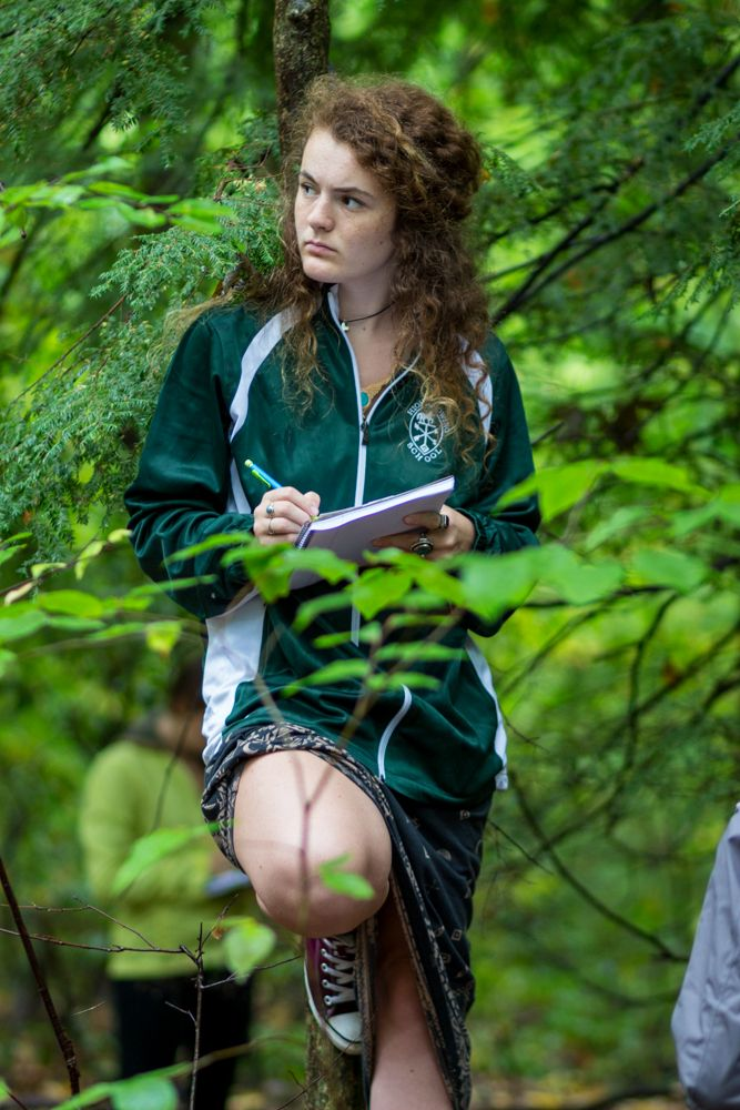 Govy Moore '17 leans against a tree, sketching the intertwined branches of the trees nearby.