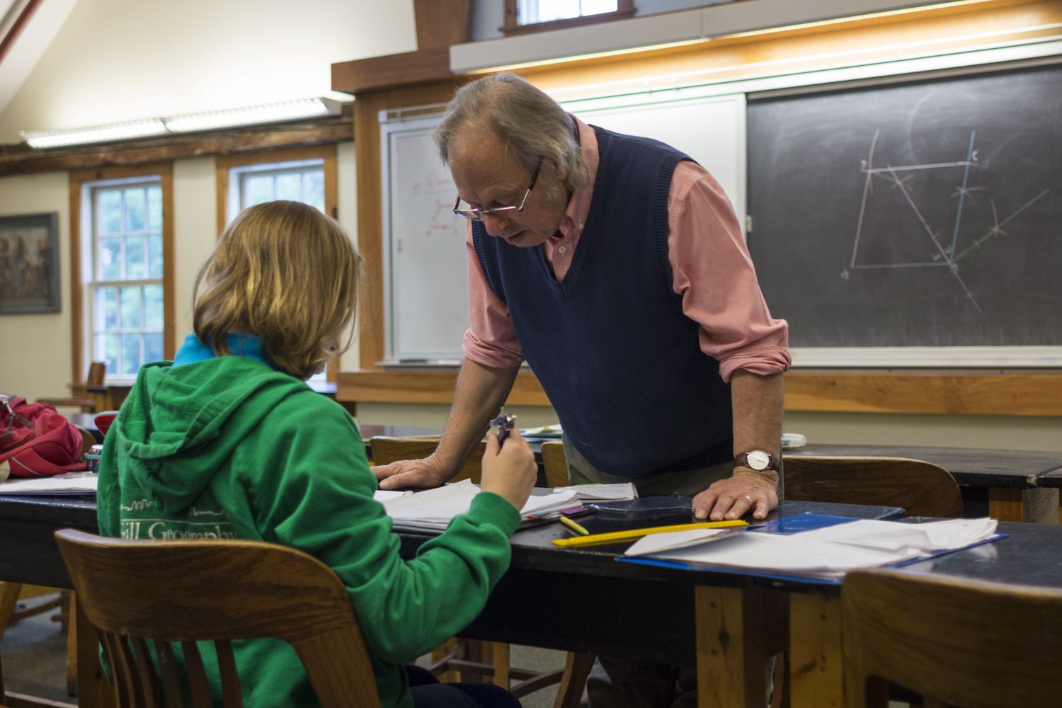 Geometry teacher Robert Sim works with Alise to solve her question.