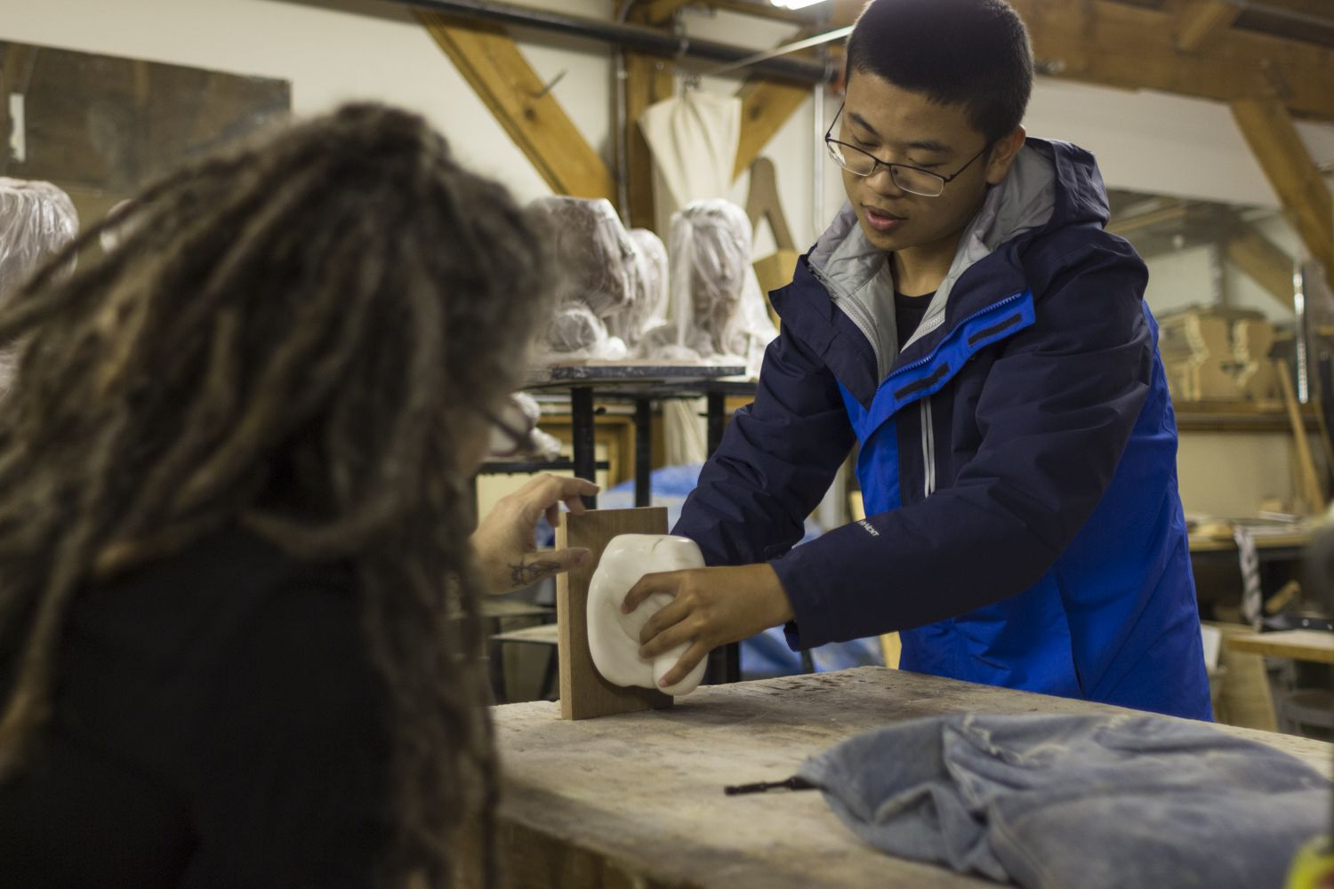 Eric Xu '19 and Material Arts teacher Michal Noer figure out the best way to mount Eric's hand-carved elephant head.