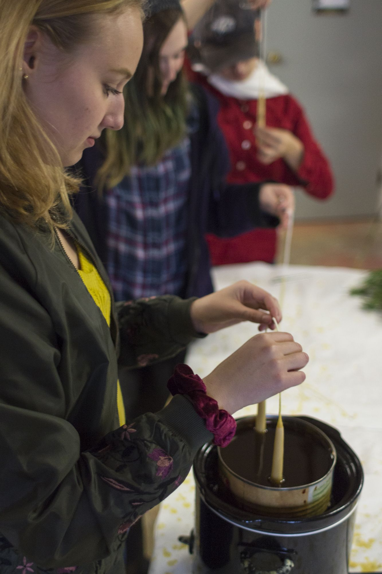 Rhianna Schahn '19 dips her half-finished candles into the steaming wax.