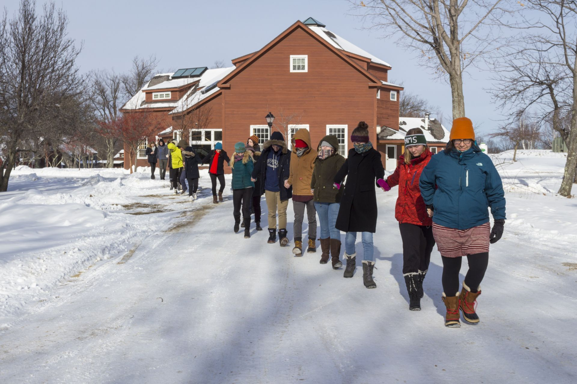 Science & Physics Teacher Laura Rubiano-Gomez leads the senior class out into the cold for a introductory exercise to their Visual Physics block class. Each student was instructed to keep their eyes shut as they were guided safely to their individual spots.