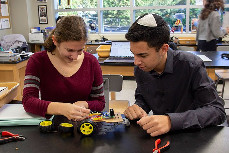 2 upper school students working on a STEM project