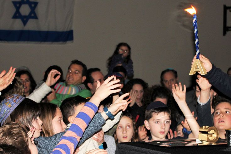 Group of children reaching for a candle - Havdalah