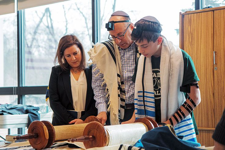2 adults and a student looking at a Torah scroll