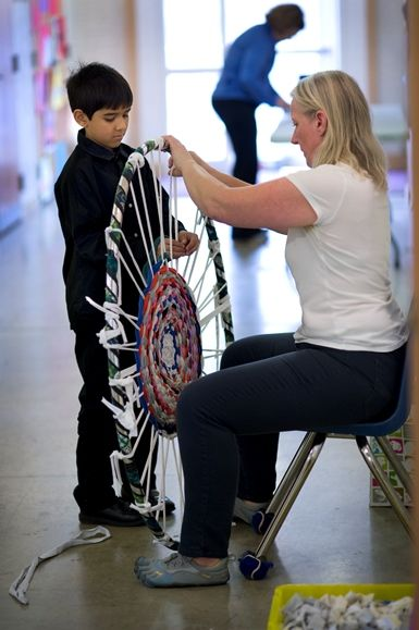 An FCS parent helps a student weave a class project for the Spring Auction.